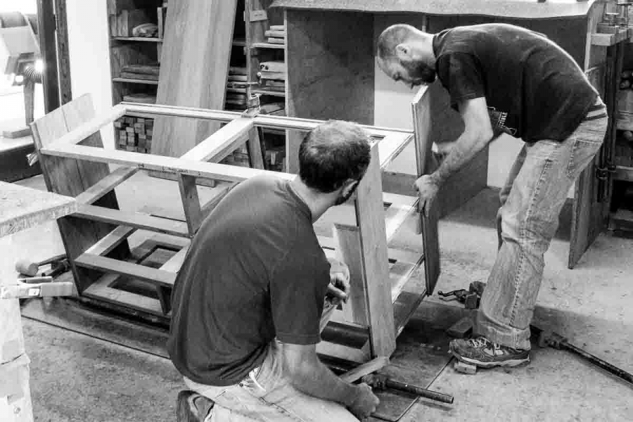 Austin and Aaron assembling cabinet ends to shelves