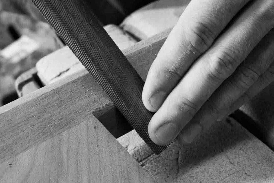 hand and rasp sculpting chair leg
