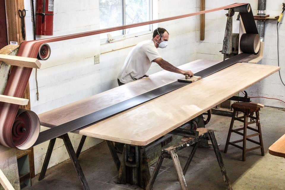Austin stroke sanding a trestle table top