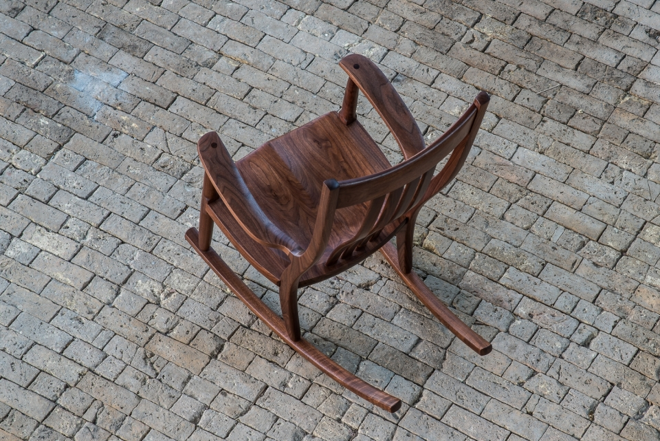walnut rocking chair on brick floor