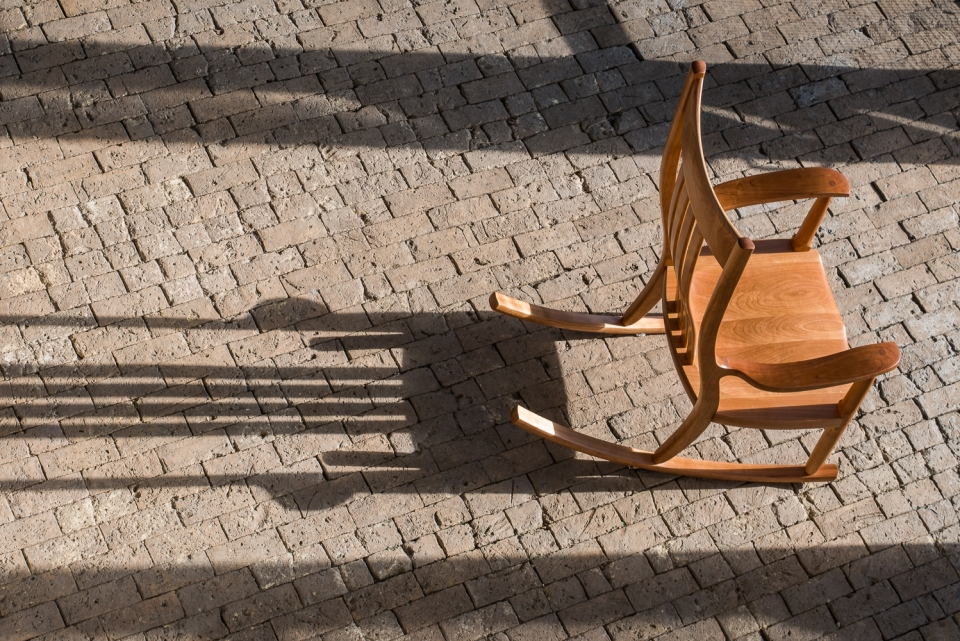 cherry rocking chair and its shadow