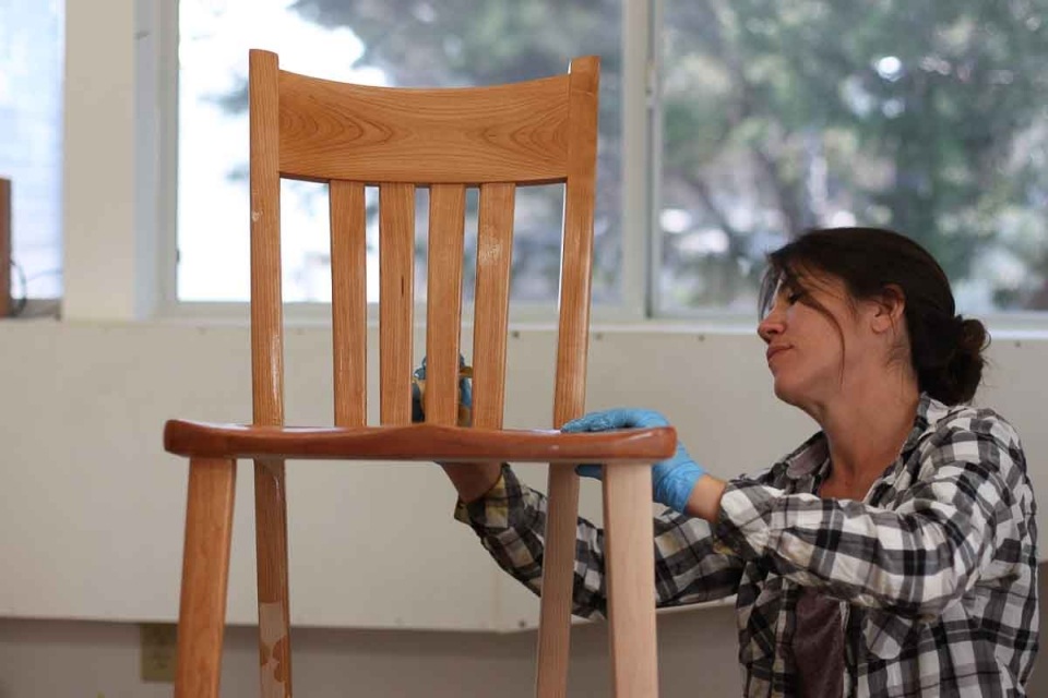 Audra oiling a cherry barstool