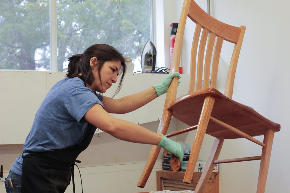 Audra finishing a dining chair