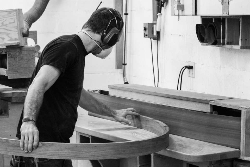 Aaron sanding a curved apron at the edge sander