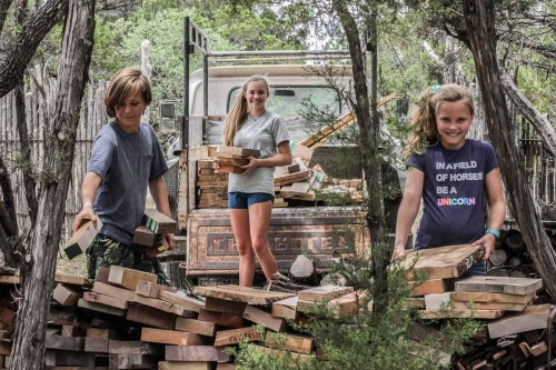 Asa, Wiley, and Bela stacking firewood