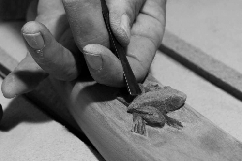 hands carving a frog
