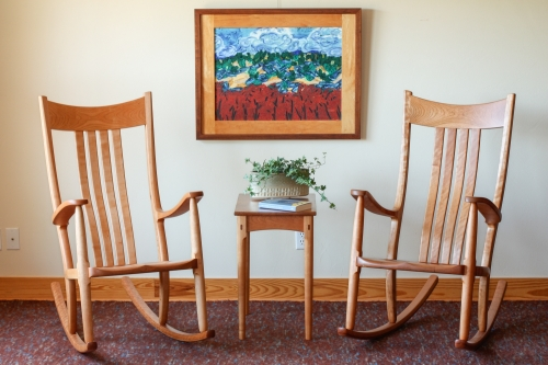 two rocking chair, a side table, and a painting