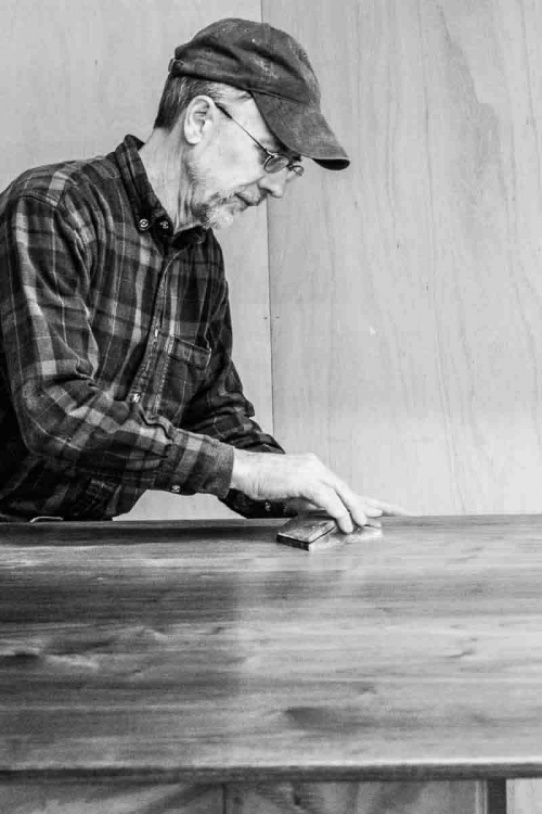 Gary sanding a table top between coats of finish